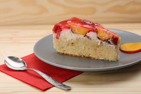 gelatina: Fresa y pastel de durazno con gelatina en la placa gris en mesa de madera Foto de archivo