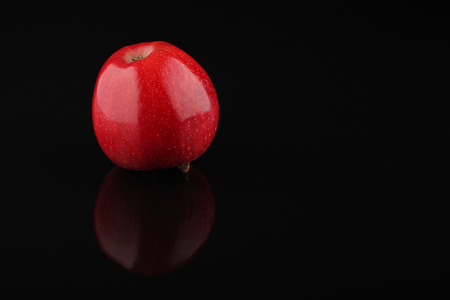 one sheet: One red apple isolated on black acrylic sheet with reflection Stock Photo