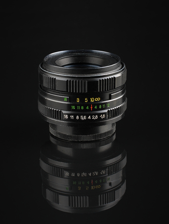 old manual lens with reflection on black acrylic sheet
