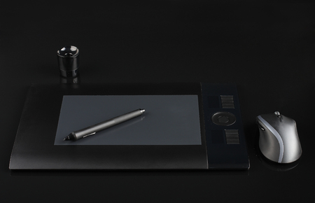 inputting: graphic tablet and pen and stand for nibs and mouse on black  background Stock Photo