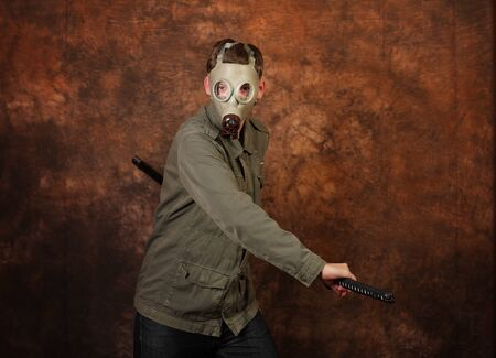 sword fight: Man with gas mask and  katana sword on brown batik background