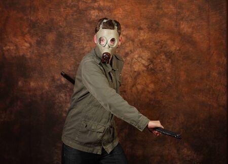 katana sword: Man with gas mask and  katana sword on brown batik background
