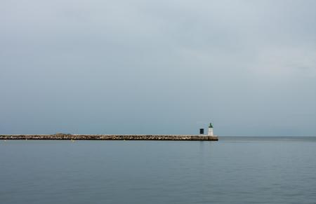 seaboard: Lighthouse on pier, on background cloudy sky.