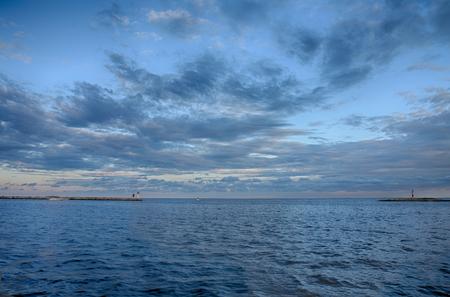 seaboard: Lighthouse on pier, ligthouse on island, on background cloudy sky. Stock Photo