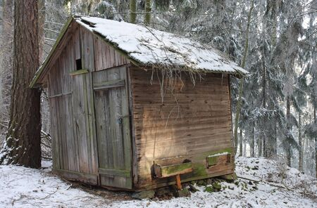 animals feeding: Wooden cottage for hay for feeding of wild animals in snowy forest Stock Photo