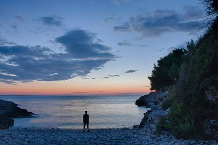 Silhouette of standing man after sea sunset