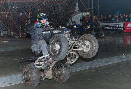quad: BRNO, CZECH REPUBLIC-MARCH 4,2016: Stuntman riding a quad bike, ATV during stunt show on International Fair for Motorcycles  on March 4,2016 in Brno in Czech Republic