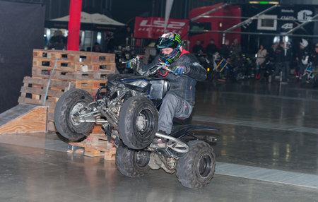 quad: BRNO, CZECH REPUBLIC-MARCH 4,2016: Stuntman riding a quad bike ATV  during stunt show on International Fair for Motorcycles  on March 4,2016 in Brno in Czech Republic Editorial