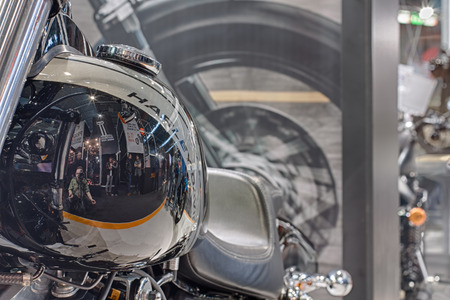 fuel tank: BRNO, CZECH REPUBLIC-MARCH 4,2016: Close up  fuel tank of motorcycle Harley Davidson Dyna Fat Bob  with reflection of visitors  on International Fair for Motorcycles on March 4,2016 in Brno in Czech Republic