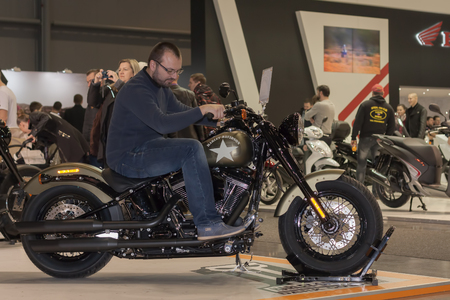 harley davidson: BRNO, CZECH REPUBLIC-MARCH 4,2016: Visitor trying to sit on  motorcycle  Harley Davidson Softail Slim  at International Fair for Motorcycles on  March 4,2016 in Brno in Czech Republic