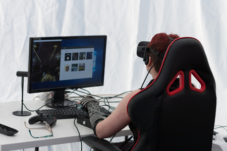 BRNO, CZECH REPUBLIC - APRIL 30, 2016: Young girl with VR - glasses sits on gaming chair and plays game on PC at Animefest, anime convention on April 30, 2016 Brno, Czech Republic Editorial