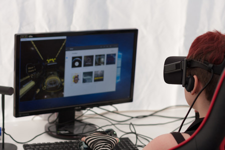 virtual reality simulator: BRNO, CZECH REPUBLIC - APRIL 30, 2016: Young girl with VR - glasses sits on gaming chair and plays game on PC at Animefest, anime convention on April 30, 2016 Brno, Czech Republic Editorial