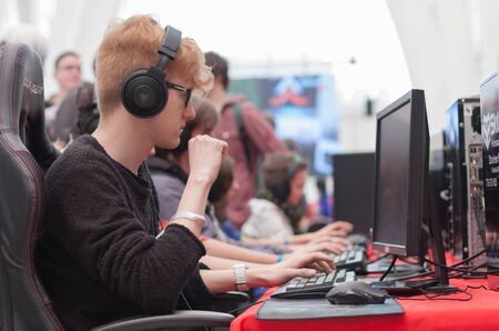 anime young: BRNO, CZECH REPUBLIC - APRIL 30, 2016: Young man sits on gaming chair and plays game on PC at Animefest, anime convention on April 30, 2016 Brno, Czech Republic
