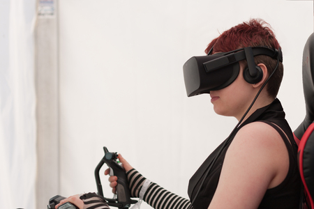 anime young: BRNO, CZECH REPUBLIC - APRIL 30, 2016: Young girl with VR - glasses sits on gaming chair and plays game on PC at Animefest, anime convention on April 30, 2016 Brno, Czech Republic Editorial