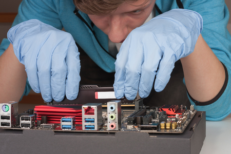 Young man with gloves  installing Ram DDR4 memory module in slot on motherboard. Stock Photo