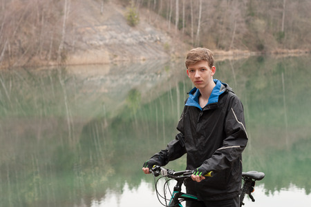 Young man relaxes on mountain bike, on background flooded mine.