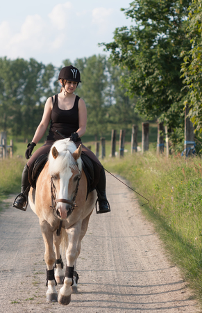 A young woman riding a horse, horse breed Haflinger.
