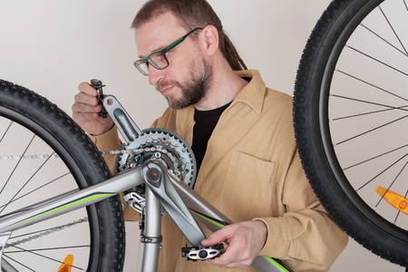 alloy: Bearded man screws the pedals on the mtb bicycle. Stock Photo