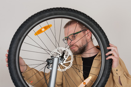 spokes: Bearded man checks the fastening of the front wheel with hydraulic disc brake on the mtb bicycle.