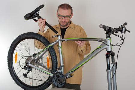 Bearded caucasian man putting a saddle on the mtb bicycle Stock Photo