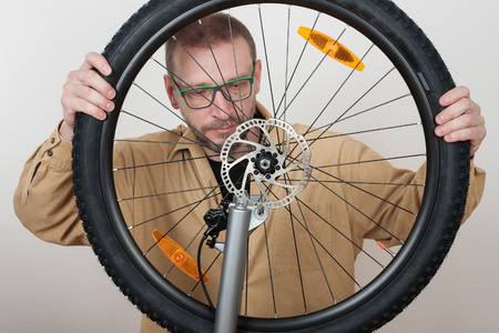 Bearded man puts the front wheel with hydraulic disc brake on the mtb bicycle.