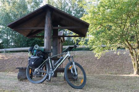 Tenda da campeggio turistica nei boschi, la bici del viaggiatore è sullo sfondo.