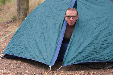 Caucasian topless man gets up in the morning in his camping tent in the woods Stock Photo