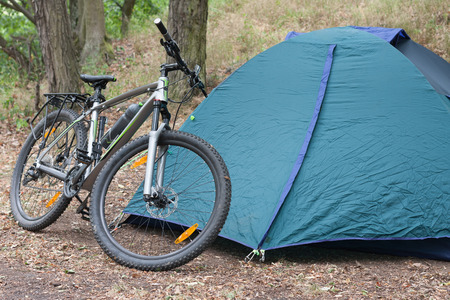 Mountain Bike In Front Of Closed Tent In The Woods In The Summer