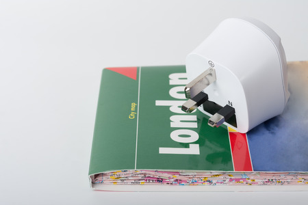White travel power adapter, European to UK and map of London. Reklamní fotografie - 85104005