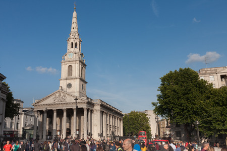 Trafalgar Square , London-September 6,2017: Tourists walking on Trafalgar Square, on background St. Martin in the Fields  on September 6, 2017 in London, United Kingdom