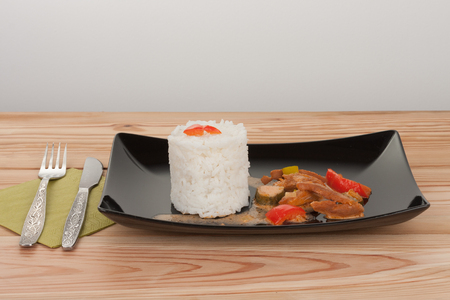 Soy noodles and rice with tomatoe sauce, paprika, cucumber and milk cream, on black plate on wooden table.  Stock Photo