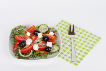 Traditional greek sallad with black olive on white plate on white background Stock Photo