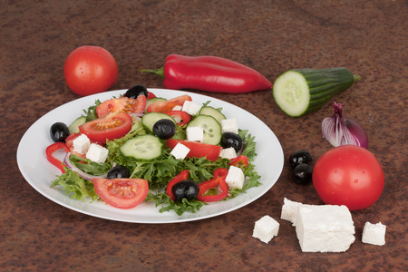 Traditional greek sallad on white plate on rusty metal sheet and ingredients for this food.