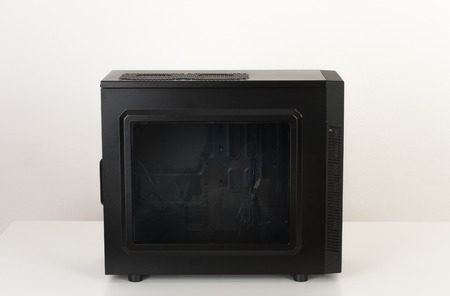 Empty black computer case, midi tower for micro ATX motherboard with transparent acryl side panel  on white table  Stock Photo