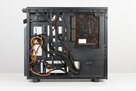 Building of PC, ATX motherboard and computer power supply unit inserted to black midi tower case