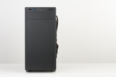 Building of PC, black computer case, midi tower for micro ATX motherboard on white table, front view without side panel.
