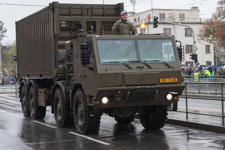 European street, Prague-October 28, 2018: Soldiers of Czech Army are riding military truck with container on military parade on October 28, 2018 in Prague, Czech Republic