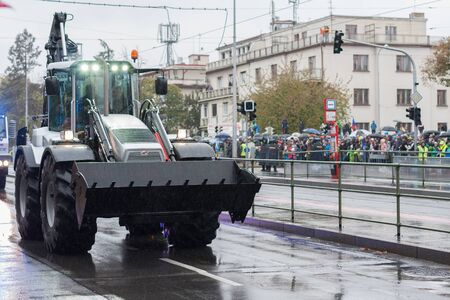 European street, Prague-October 28, 2018: Police workers are riding backhoe loader on military parade on October 28, 2018 in Prague, Czech Republic