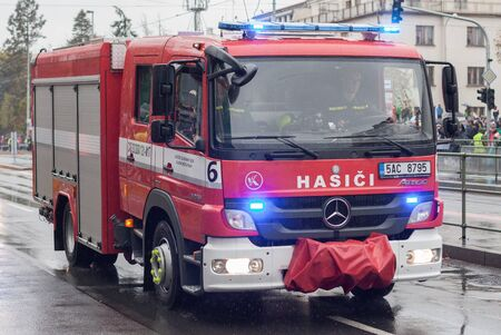 European street, Prague-October 28, 2018: Fire brigade workers are riding fire truck on military parade on October 28, 2018 in Prague, Czech Republic 에디토리얼