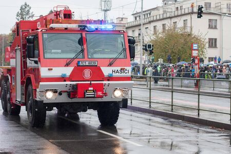 European street, Prague-October 28, 2018: Fire brigade workers are riding fire truck crane on military parade on October 28, 2018 in Prague, Czech Republic