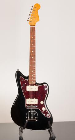 Black electric guitar, studio shoot. Red tortoise shell pickguard, alder body, maple neck, two single coil.