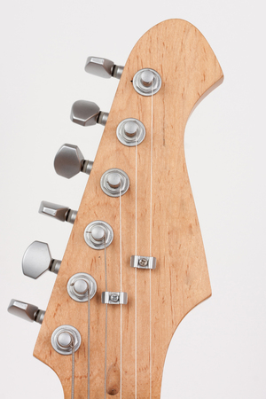 Close up of lightweight chrome tuning machines on neck of electric guitar, studio shoot. Stock Photo