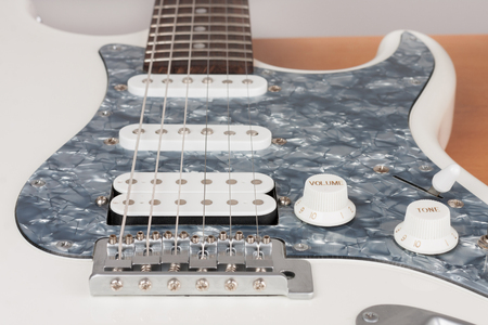 Part of white electric guitar, studio shoot.  2 x Single Coil and 1 x Humbucking. Black Pearl pickguard, Rosewood Fingerboard