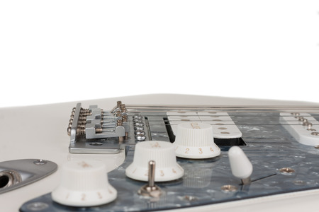 Close up of bridge  of white electric guitar, studio shoot.  2 x Single Coil and 1 x Humbucking. Black Pearl pickguard