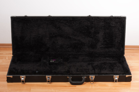 Black leather case for electric guitar on the floor in living room. Inside of case electronic tuner.