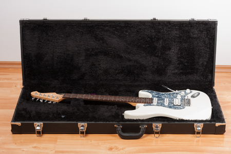 White electric guitar in black leather case.  2 x Single Coil and 1 x Humbucking. Black Pearl pickguard, Rosewood Fingerboard