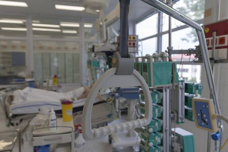 Hospital bed trapeze, on background patient connected to medical ventilator in ICU in hospital, a place where can be treated patients with pneumonia caused by coronavirus covid- 19. Stock Photo