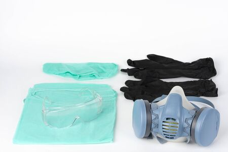 Twin filter half face respirator mask, plastic protective eyglasses, protective gown, cap, pair of gloves,  personal protective equipment to protect against the virus covid-19.