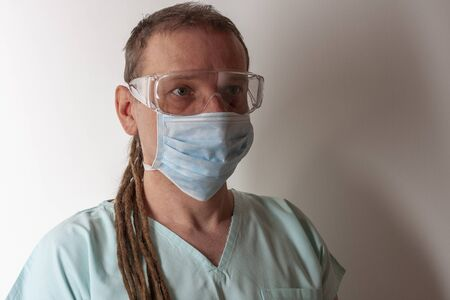 Male nurse, with plastic protective eyeglasses and face mask , with  personal protective equipment to protect against the virus covid-19 in ICU in hospital. Stock Photo
