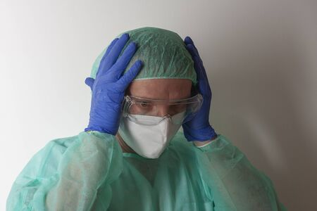 Male nurse, with plastic protective eyeglasses and respirator ffp2, cap, gown, gloves, with personal protective equipment to protect against the virus covid-19 in ICU in hospital.